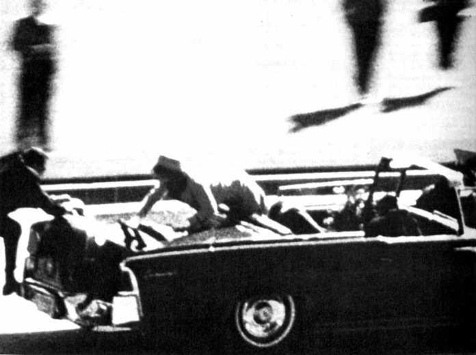 Jacqueline Kennedy intenta escapar del punto de mira del tirador que acaba de herir mortalmente a su marido