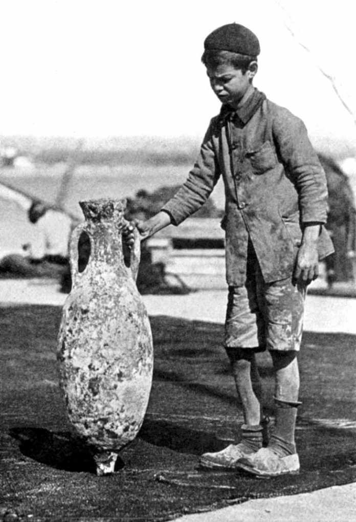 Un joven pescador ibicenco sostiene un ánfora, en una foto de 1928