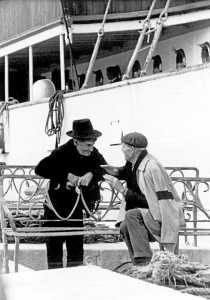 Dos hombres conversando en el puerto. Albert Schwarz