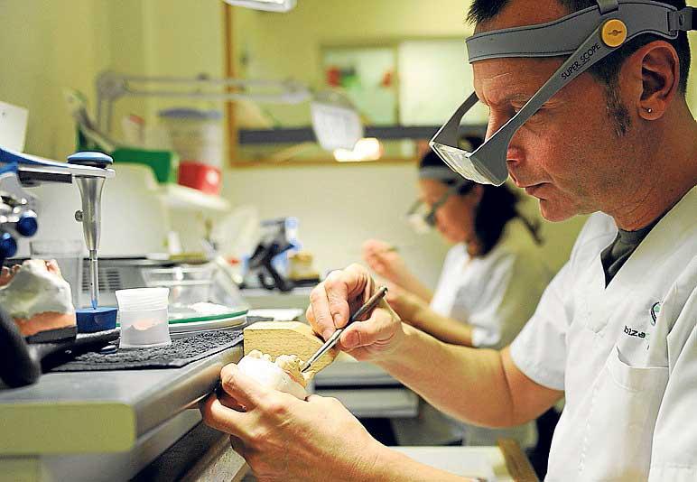 Dos técnicos confeccionan prótesis en cerámica en el laboratorio.