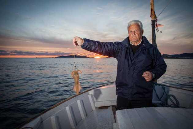 El pescador Joan Marí muestra un calamar pescado con potera en una imagen de archivo. VICENT MARÍ