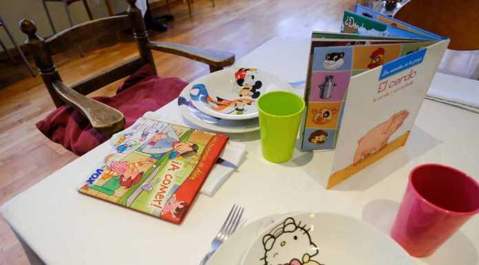 Restaurants Amics de la Infància, con vajilla infantil, cuentos y una trona dispuesta en la mesa