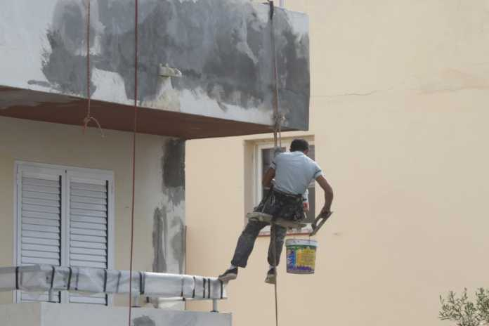 Un operario pinta la fachada de un edificio en Ibiza.