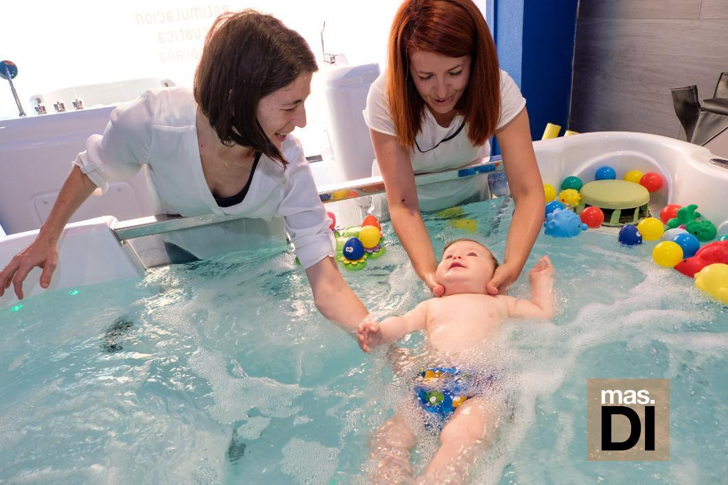 Una profesional del centro explica a una mamá las técnicas de la estimulación acuática.