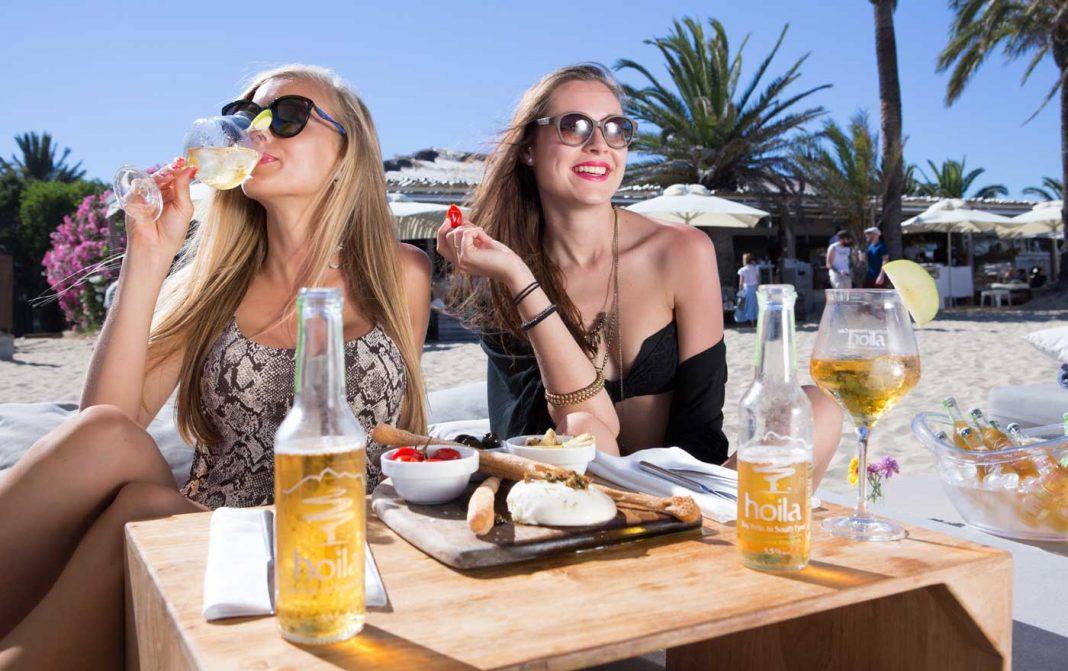 Dos jóvenes turistas disfrutando de una bebida en un 'beach club' sobre la fina arena de una playa. AISHA BONET