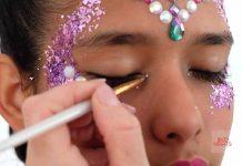 Joyas y el glitter. Una profesional coloca una perla en forma de lágrima como parte de su maquillaje.