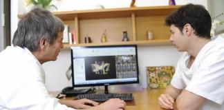 Padre e hijo estudian en el ordenador un caso que se trata en la clínica. | GABI VÁZQUEZ