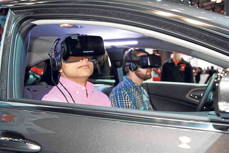 Dos asistentes en el 2015 Chrysler 200 visualizan en realidad virtual el funcionamiento del coche.
