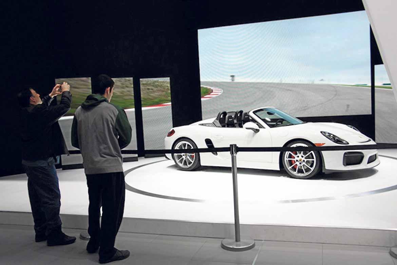 Dos visitantes admiran el Porsche Cayman 2015.