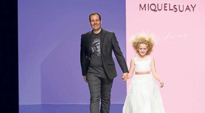 El diseñador Miquel Suay con una de las pequeñas modelos en la última Barcelona BridalWeek. BARCELONA BRIDALWEEK