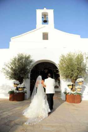 [:es]La novia con el padrino en la entrada decorada con cestos y flores.[:]