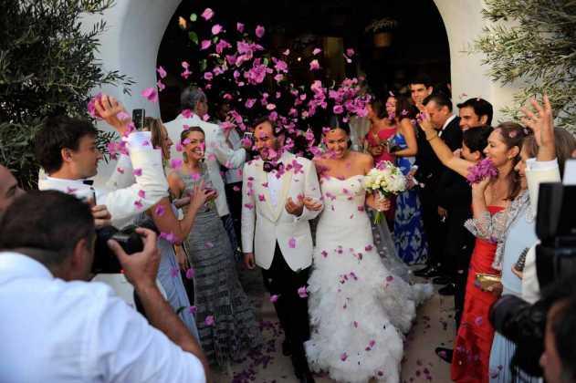 [:es]Los invitados felicitan con pétalos de flores a los recien casados a la salida de la parroquia.[:]