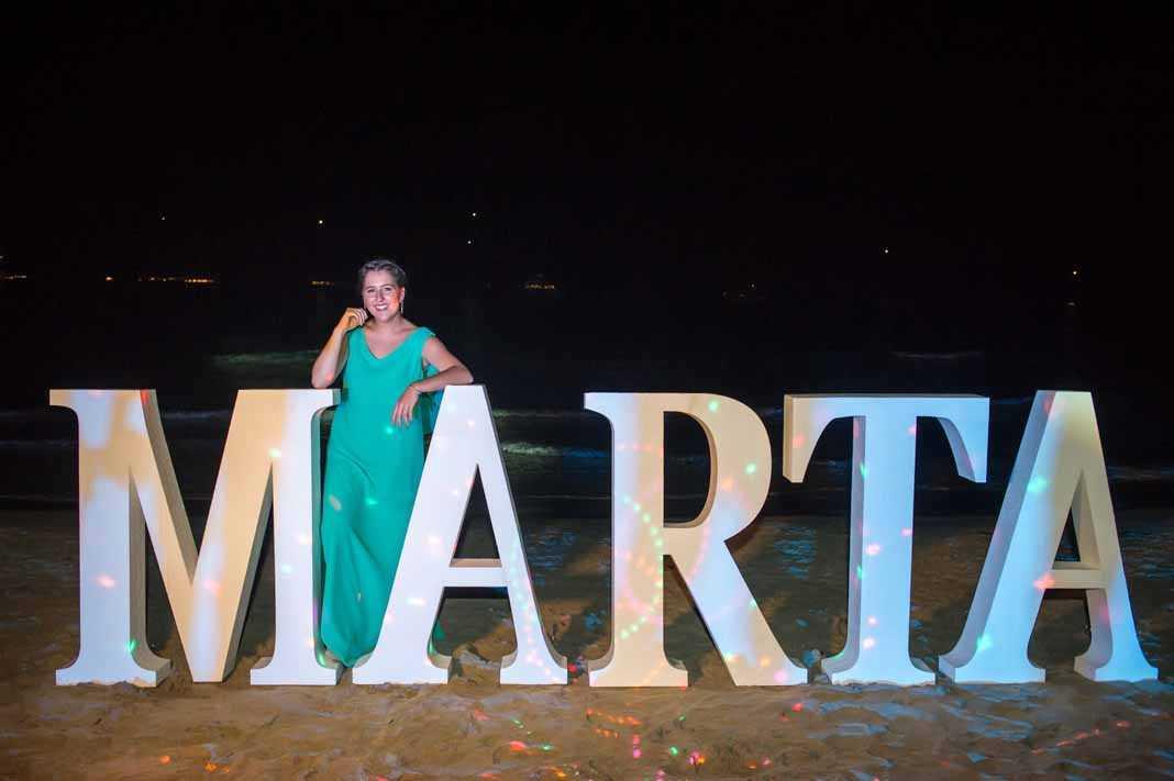 [:es]Marta Pérez Maura posa ante el cartel situado en la playa con su nombre y efectos especiales. FOTOS SERGIO CAÑIZARES.[:]