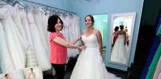 Mariluz Serra junto a una novia probándose uno de los vestidos de la tienda. FOTOS RUBÉN E, IBAÑEZ