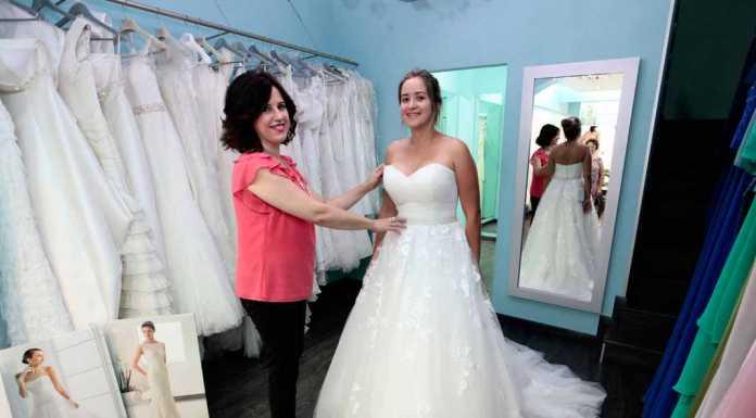 [:es]Mariluz Serra junto a una novia probándose uno de los vestidos de la tienda. FOTOS RUBÉN E, IBAÑEZ[:]