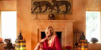 La exmodelo italiana Isa Stoppi posa ante la chimenea de su casa ibicenca flanqueda por sus perros.