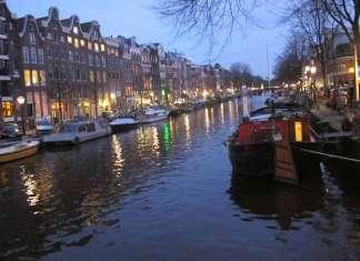 Iluminación navideña. Panorámica de vista nocturna del canal Pinsengracht con los árboles, casas y barcos decorados con 'leds' de colores. J.S.