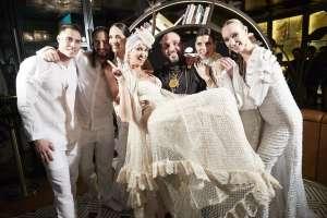 El diseñador Tony Bonet lleva en brazos a una modelo vestida de novia.